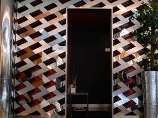 stěna oddělující WC od hlavní recepce složená z různých druhů ušlechtilých materiálů